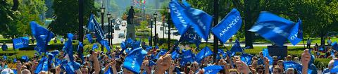 A group of AMAPCEO members in front of Queen's Park with AMAPCEO flags