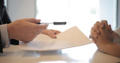 Photo of hands holding a stack of papers and a pen and another pair of hands crossed