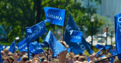 Photo of many small AMAPCEO flags being waved by a crowd